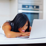 Young asian woman sitting with her laptop in the kitchen at home